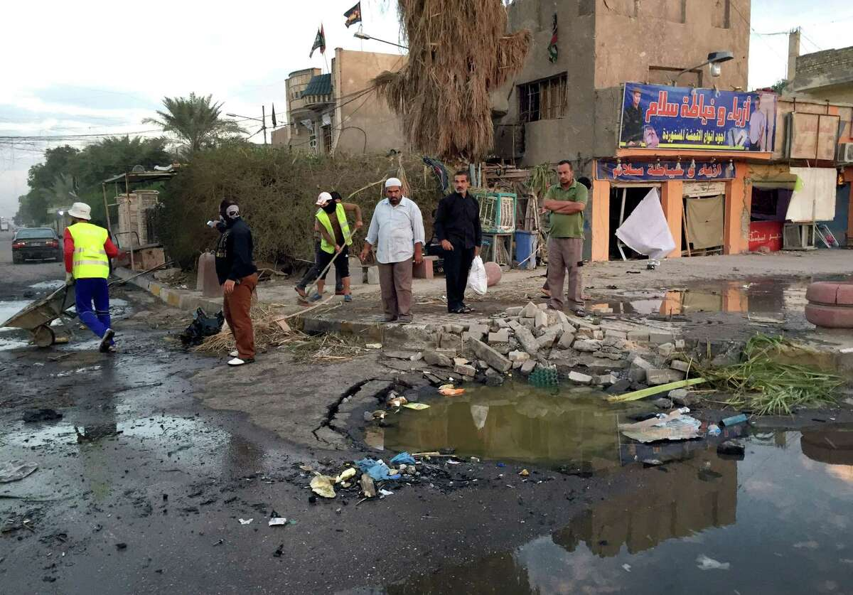 Iraqi civilians gather the morning after a car bombing in Baghdad, Iraq, Monday, Nov. 3, 2014. A car bomb targeting Shiite pilgrims killed and wounded scores of people late Sunday in Baghdad's eastern district of Sadr City, authorities said. (AP Photo/Ali Abdul Hassan)