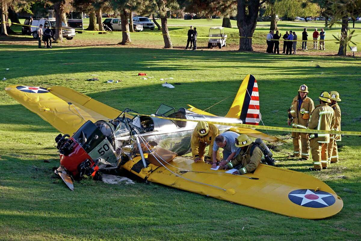 Officials work on the scene of a vintage airplane that crash-landed on the Penmar Golf Course in the Venice area of Los Angeles, Thursday, March 5, 2015. Harrison Ford crash-landed the airplane shortly after taking off from a nearby airport and reporting engine problems. (AP Photo/Damian Dovarganes)