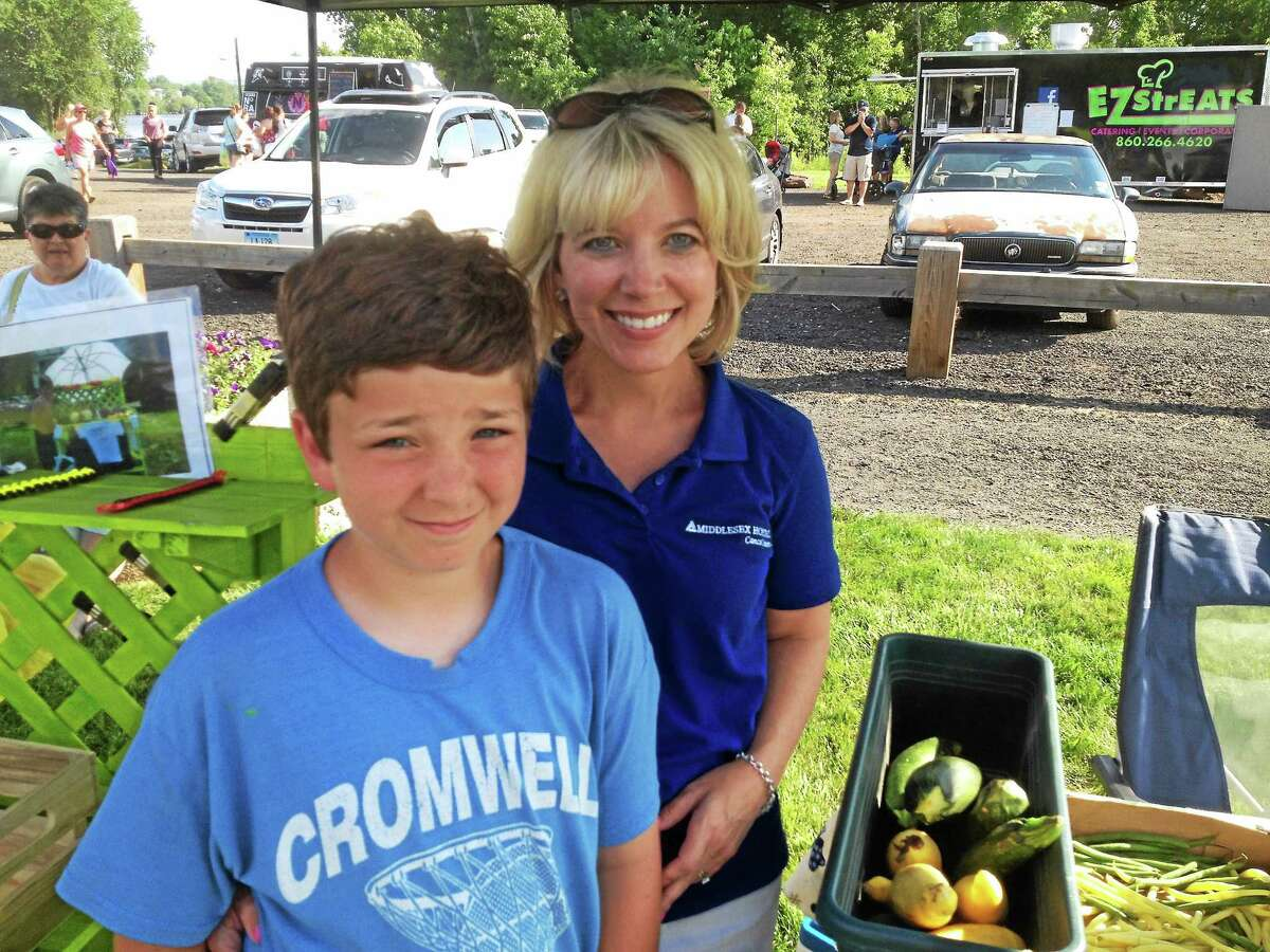 Tanner and his mother Beth Slifer of Cromwell run a vegetable booth at the weekly farmers market. The boy came up with the idea to sell extra produce from his grandfather's garden to raise funds for the holiday food drive at the Middlesex Hospital Cancer Center in Middletown.