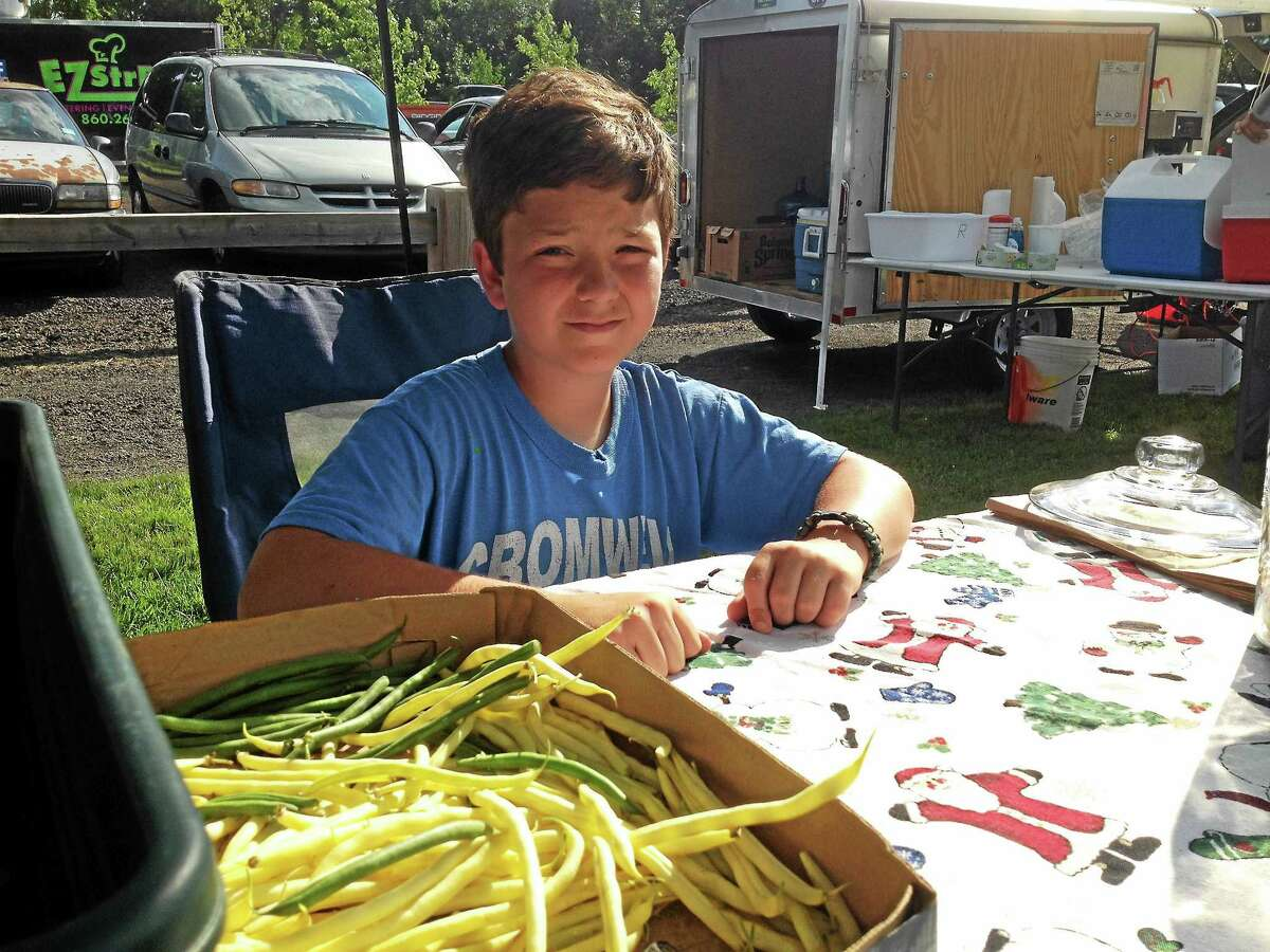 Tanner Slifer, 12, of Cromwell sells yellow wax and green beans at the weekly town market.