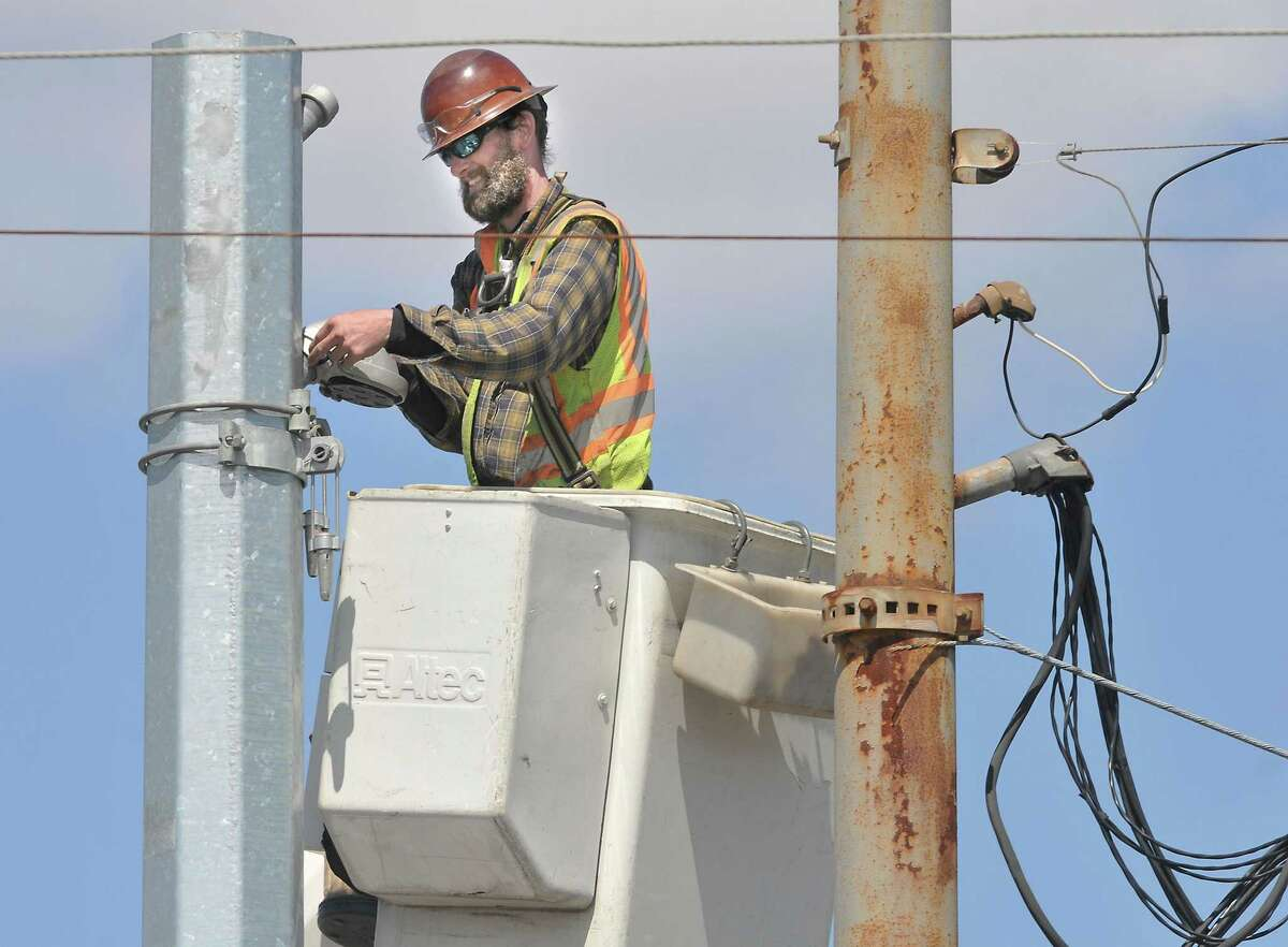 Sean Bailor, employed by Connecticut Light & Power installs a new light on Main Street in Durham in this file photo.