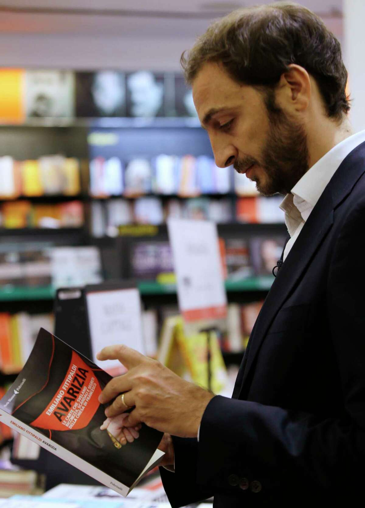 """Italian journalist Emiliano Fittipaldi browses through his book titled """" Avarice"""" during an interview with The Associated Press, in a Rome's bookstore, Tuesday, Nov. 3, 2015. The Vatican's new leaks scandal intensified Tuesday with two books detailing the mismanagement and internal resistance that is thwarting Pope Francis' financial reform efforts: 'Avarice' by L'Espresso Vatican reporter Emiliano Fittipaldi and 'Merchants in the Temple' by Italian journalist Gianluigi Nuzzi. (AP Photo/Gregorio Borgia)"""