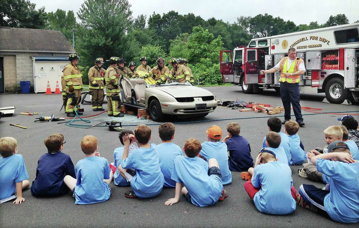 Cromwell Fire Chief Stephen Pendl explains to Cub Scouts from six troops including Pack 9 of Cromwell what happens after a car accident Tuesday morning at Pierson Park.