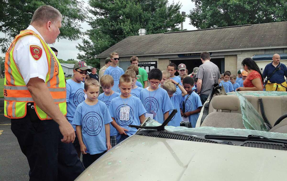 Cromwell Fire Chief Stephen Pendl and other Cromwell firefighters show Cub Scouts from six troops including Pack 9 of Cromwell the aftermath of a car extrication Tuesday morning at Pierson Park.