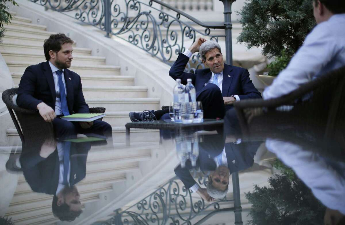 U.S. Secretary of State John Kerry, centre, and State Department Chief of Staff Jon Finer, left, meet with members of the U.S. delegation Friday at the garden of the Palais Coburg hotel where the Iran nuclear talks meetings are being held in Vienna, Austria.