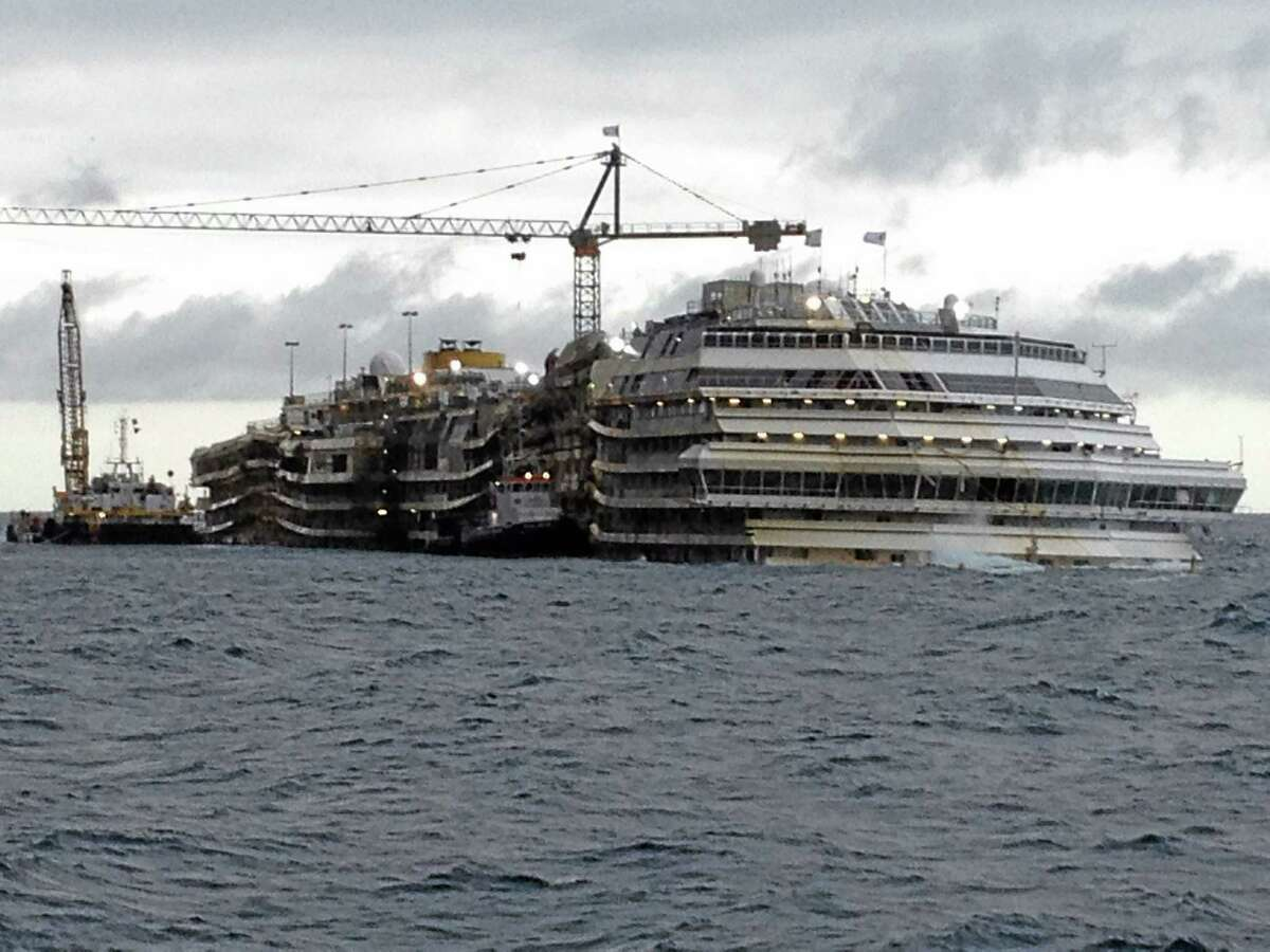 The Costa Concordia cruise liner lies in the waters of the Giglio Island, Italy, Thursday, Jan. 23, 2014. Experts boarded the Costa Concordia cruise liner to investigate whether there is more to the shipís sinking than is contained in prosecutorsí case against its captain. A team on Thursday examined the bridge of the cruise liner that sank Jan. 13, 2012 with thousands aboard, killing 32, to investigate if any factors beyond human error contributed to the shipwreck. Experts are to return next month to look at the linerís emergency generator. A judge granted a joint request for the onboard evaluation to collect evidence sought by Capt. Francesco Schettinoís defense and a consumer group representing victims. So far, Schettino is the only person being tried although his defense and others contend that Costa Crociere SpA, the shipís owner, bears some responsibility. (AP Photo/Luigi Navarra)