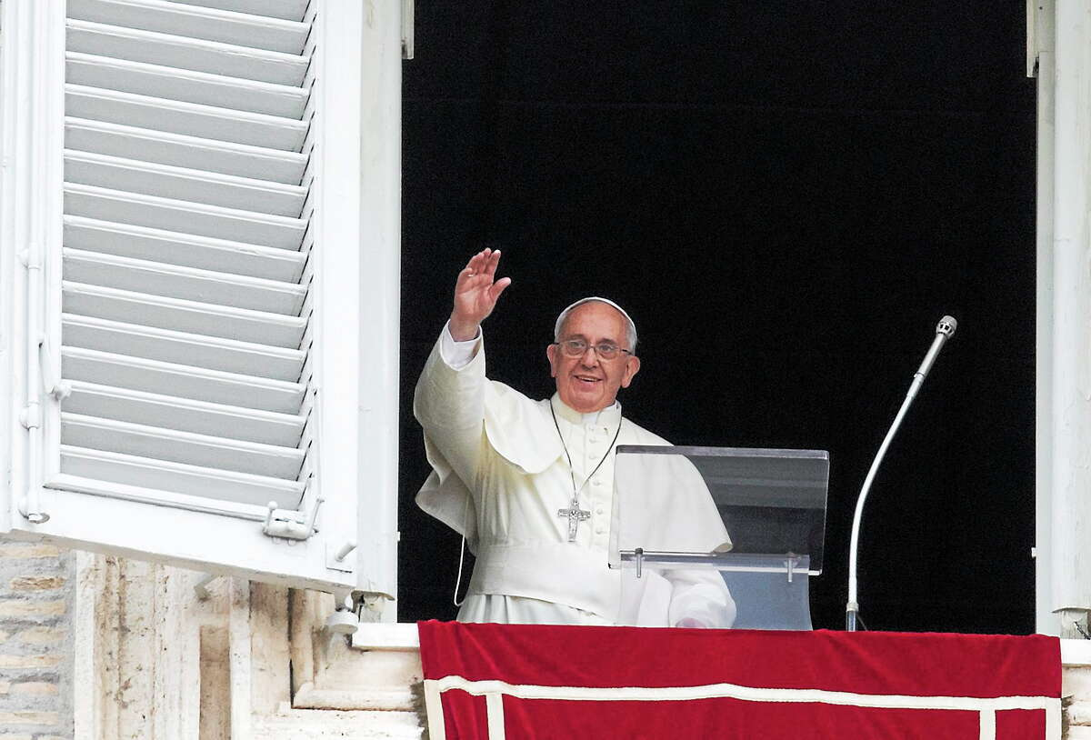 Pope Francis waves as he arrives for the Angelus prayer he delivers from the studio window overlooking St. Peter square at the Vatican on July 13, 2014.