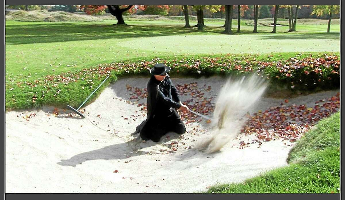 Art Decko's alter ego, El Cabon, hits a shot out of a bunker from his knees at the Mohegan Sun Golf Club.