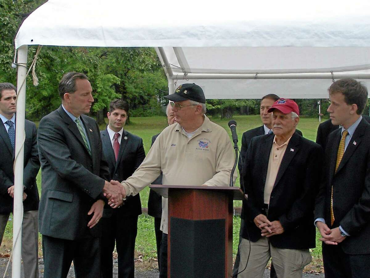 In this 2012 photograph, state Sen. Paul Doyle, who spearheaded the effort to secure funding for the city's military museum three years ago, shakes hands with Ron Organek, president of the Greater Middletown Military Museum Board of Directors while Phil Cacciola, vice president of the museum board of directors and state Rep. Matt Lesser look on during a press conference to announce a $300,000 state grant.