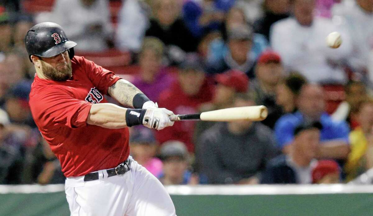 Red Sox first baseman Mike Napoli connects on a two-run double against the Cleveland Indians during a June 13 game at Fenway Park in Boston.