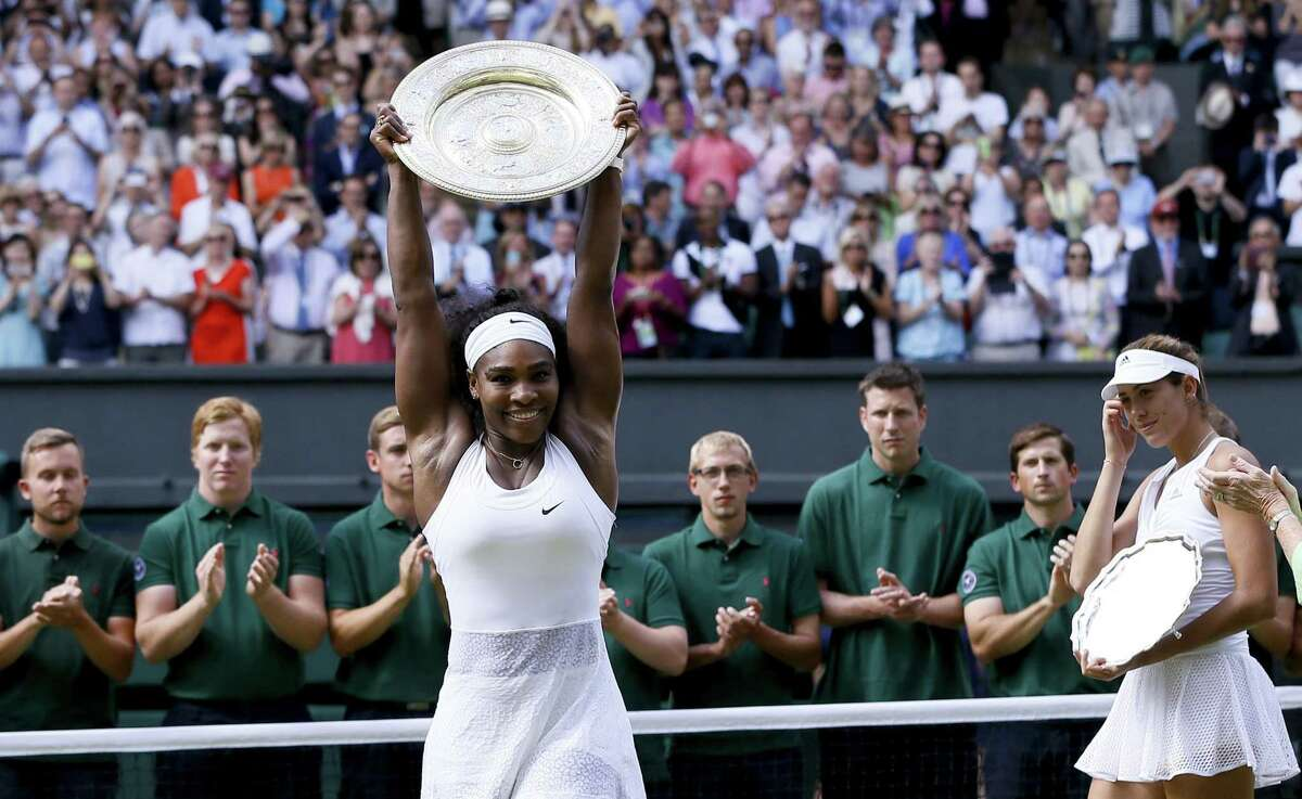Serena Williams holds up the trophy after winning the final against Garbine Muguruza, background, on Saturday at the All England Lawn Tennis Championships in Wimbledon, London. Register sports columnist Chip Malafronte says Serena is, hands down, the greatest female athlete of all time.