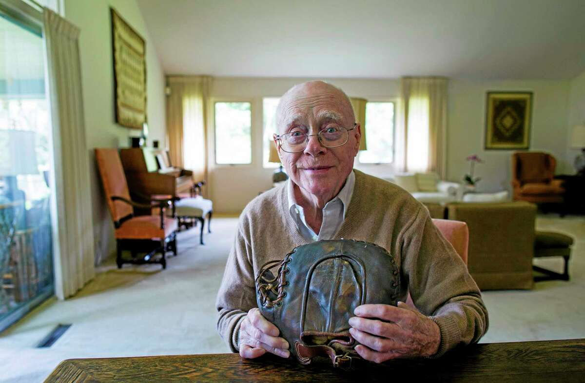 In this photo taken on Monday, June 30, 2014, Howard Henderson, who as a boy in New York played catch with baseball legend Lou Gehrig, holds a signed baseman's mitt given to him by Gehrig when he was young, at Henderson's Greenwich, Conn., home.