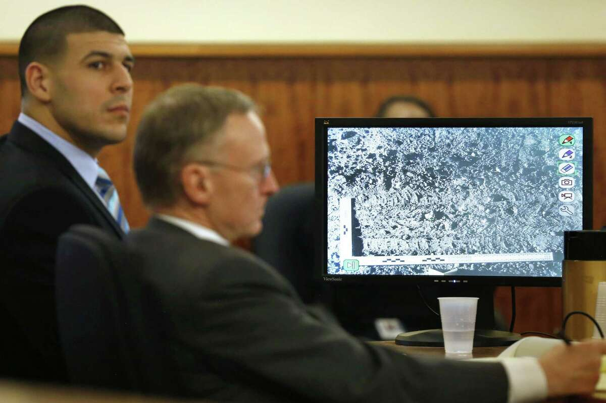 Former New England Patriots football player Aaron Hernandez, left, sits with his defense attorney Charles Rankin, center, as a photograph of tire marks is displayed on a monitor during Hernandez's murder trial Thursday in Fall River, Mass.