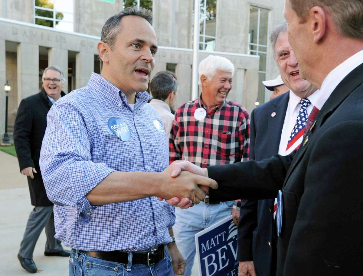 In a Oct. 29 file photo, Republican gubernatorial candidate Matt Bevin, left, talks to people following the Greater Owensboro Chamber of Commerce's Red, White and Blue Picnic on the lawn of the Daviess County Courthouse, in Owensboro, Ky.