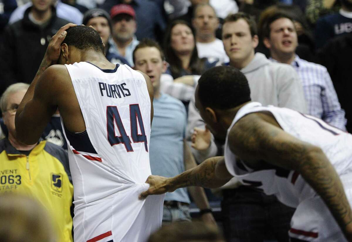 UConn's Ryan Boatright, right, grabs teammate Rodney Purvis as he walks off the court holding his head during the first half of Thursday's game against Memphis. Purvis took a hard fall on his head resulting in a flagrant foul against Memphis' Calvin Godfrey. Memphis won 54-53.