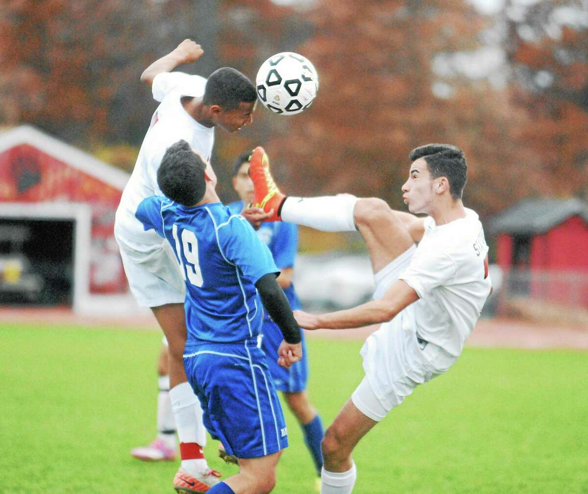 Cromwell junior Jared Grant puts his head on the ball as teammate Ardit Statovci tries to kick it on goal. Defending is Old Saybrook's Ben VanVliet (19).