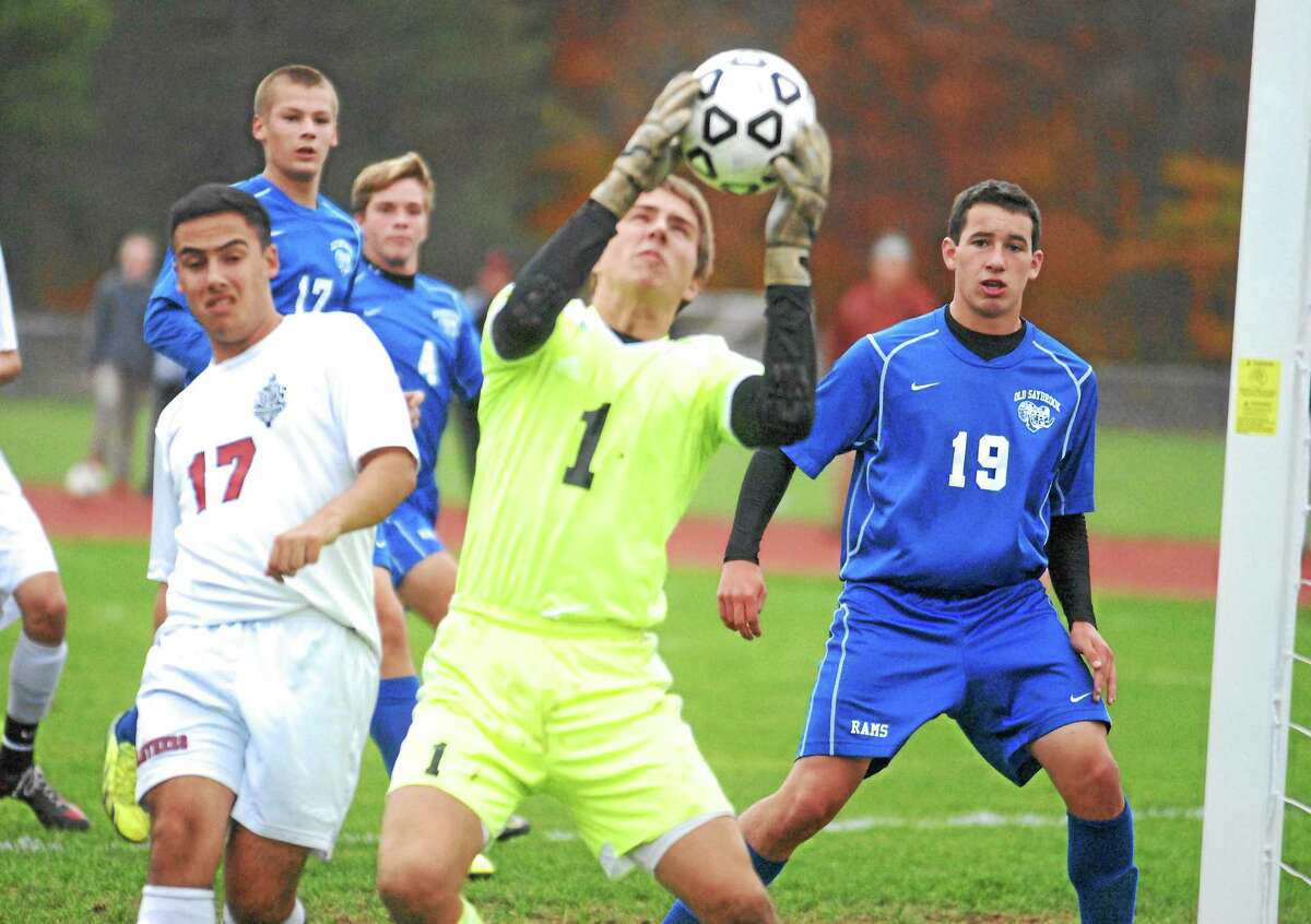 Old Saybrook junior keeper Lucas Sumby makes the save as Cromwell's Austin Jacinto (17) and Old Saybrook's Ben VanVliet (19) look on.