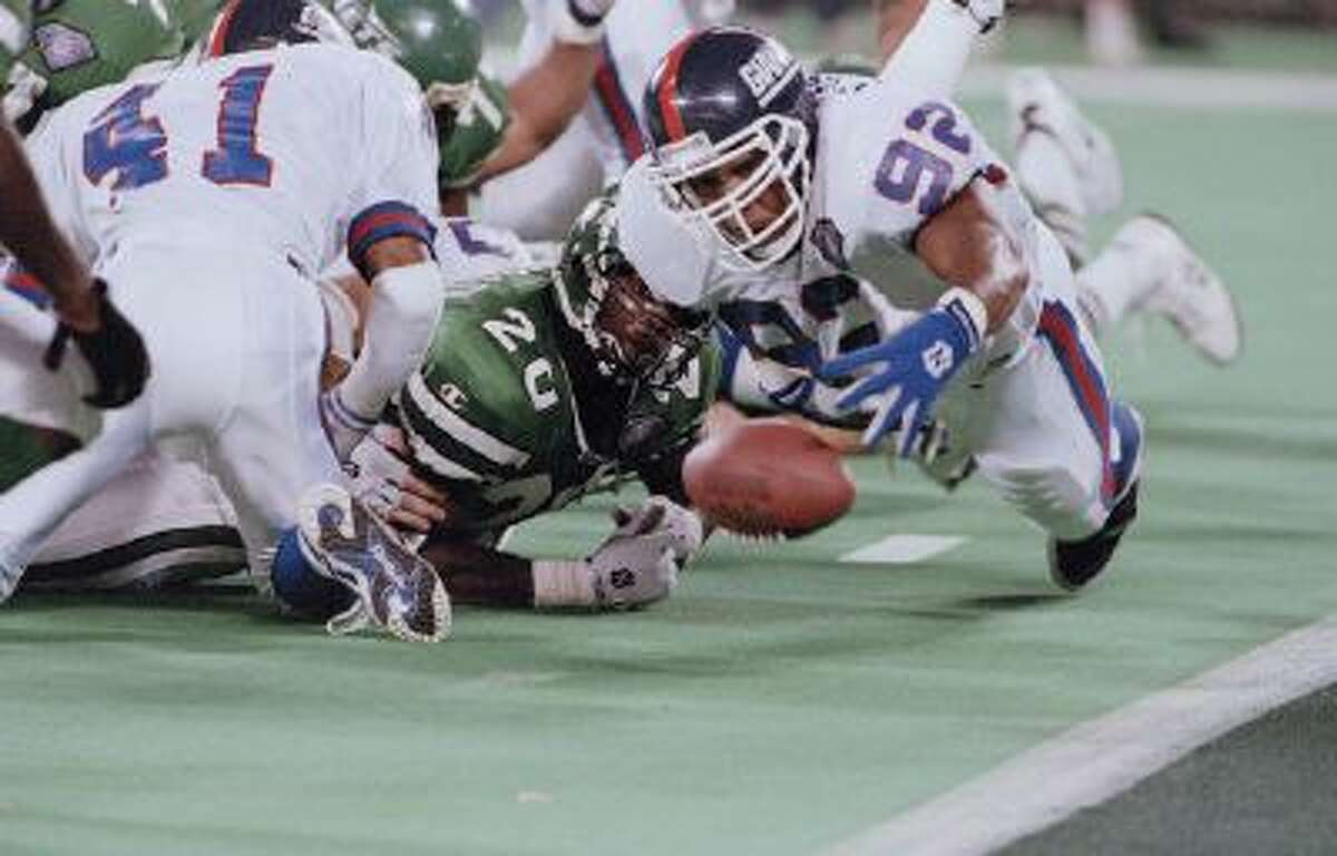 New York Giants defensive end Michael Strahan (92) recovers a fumble by New York Jets running back Richie Anderson, left, in the fourth quarter at Giants Stadium in East Rutherford, N.J., Aug. 20, 1994.