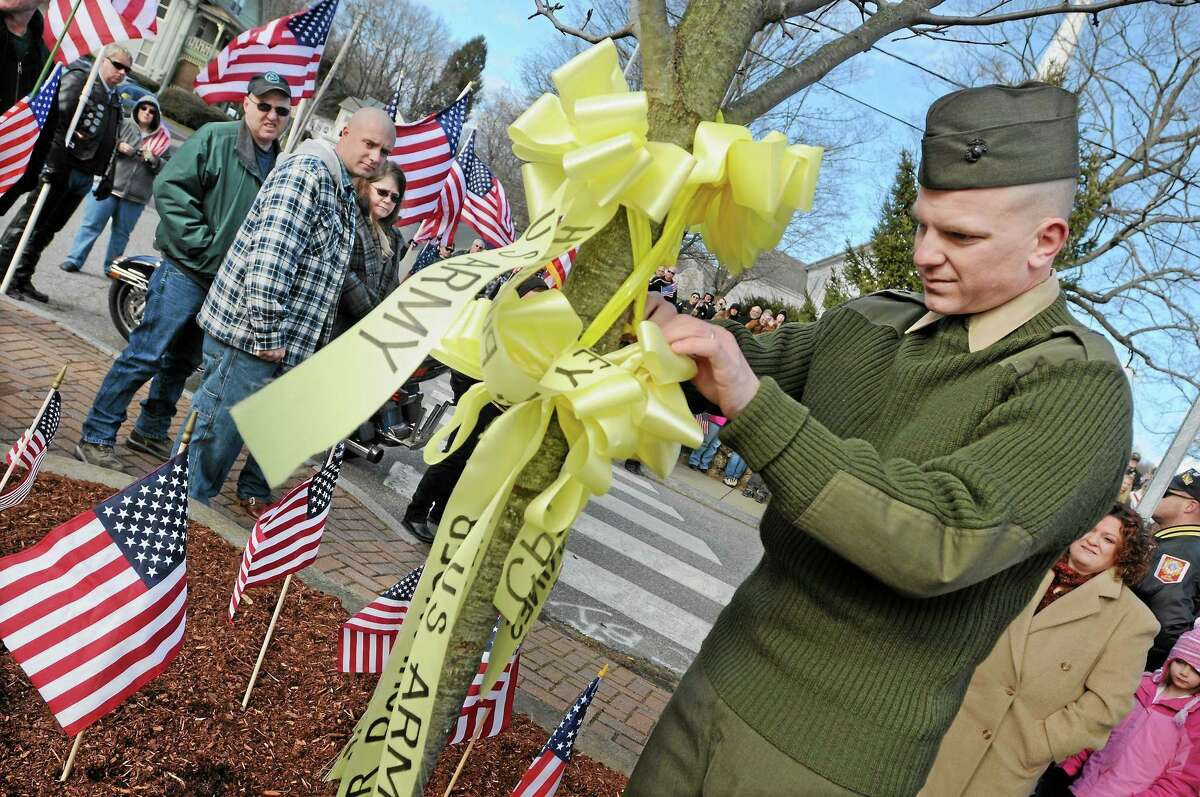 Lance Cpl. Anthony Strong removes a yellow ribbon from a tree at the village center in East Hampton at a homecoming celebration in January 2012 after returning from Afghanistan.