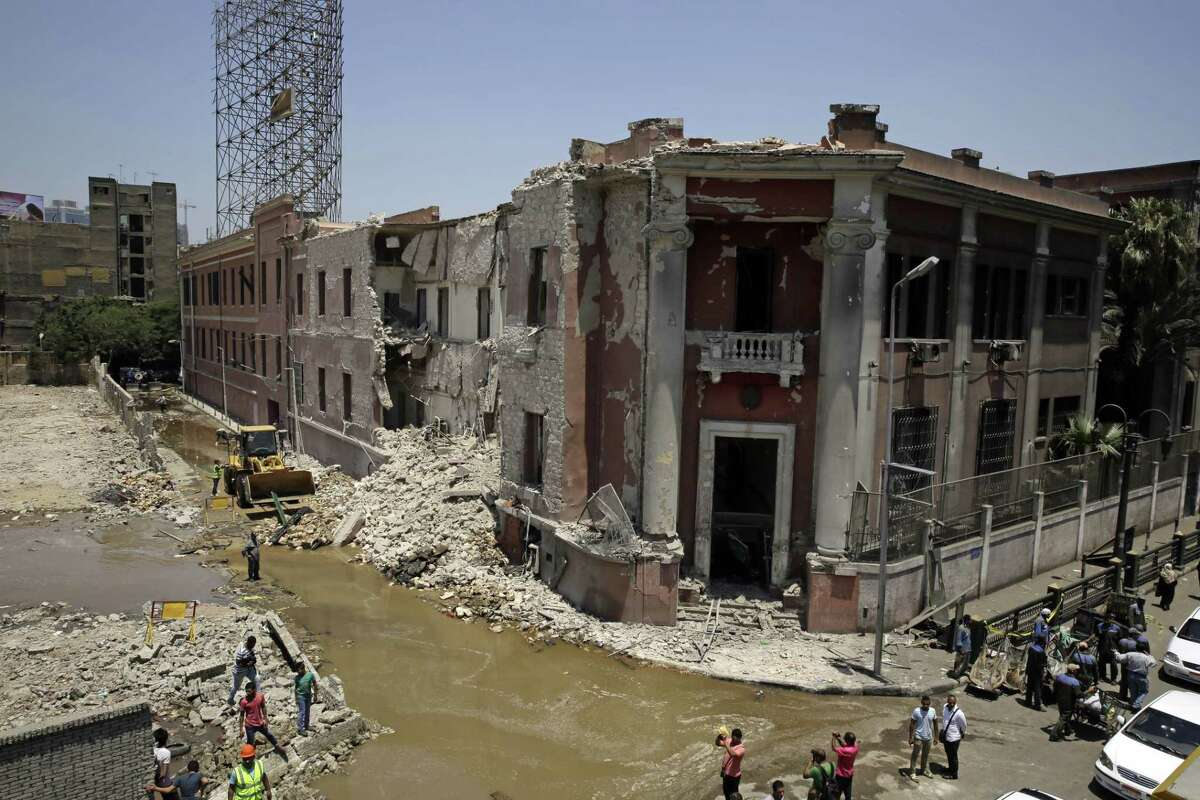 Workers clear rubble at the site of an explosion near the Italian Consulate in downtown, Cairo, Egypt, Saturday, July 11, 2015. Italy's foreign minister vowed that his country would not be intimidated after a deadly explosion Saturday morning killed one person and heavily damaged the Italian Consulate in the Egyptian capital.