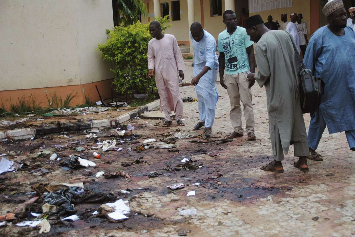 In this file photo from July 7, people look at the site of another Boko attack. A bomb blast at a university in Zaria, Nigeria, killed dozens, including a 2-year-old toddler, the Kaduna state governor reported.