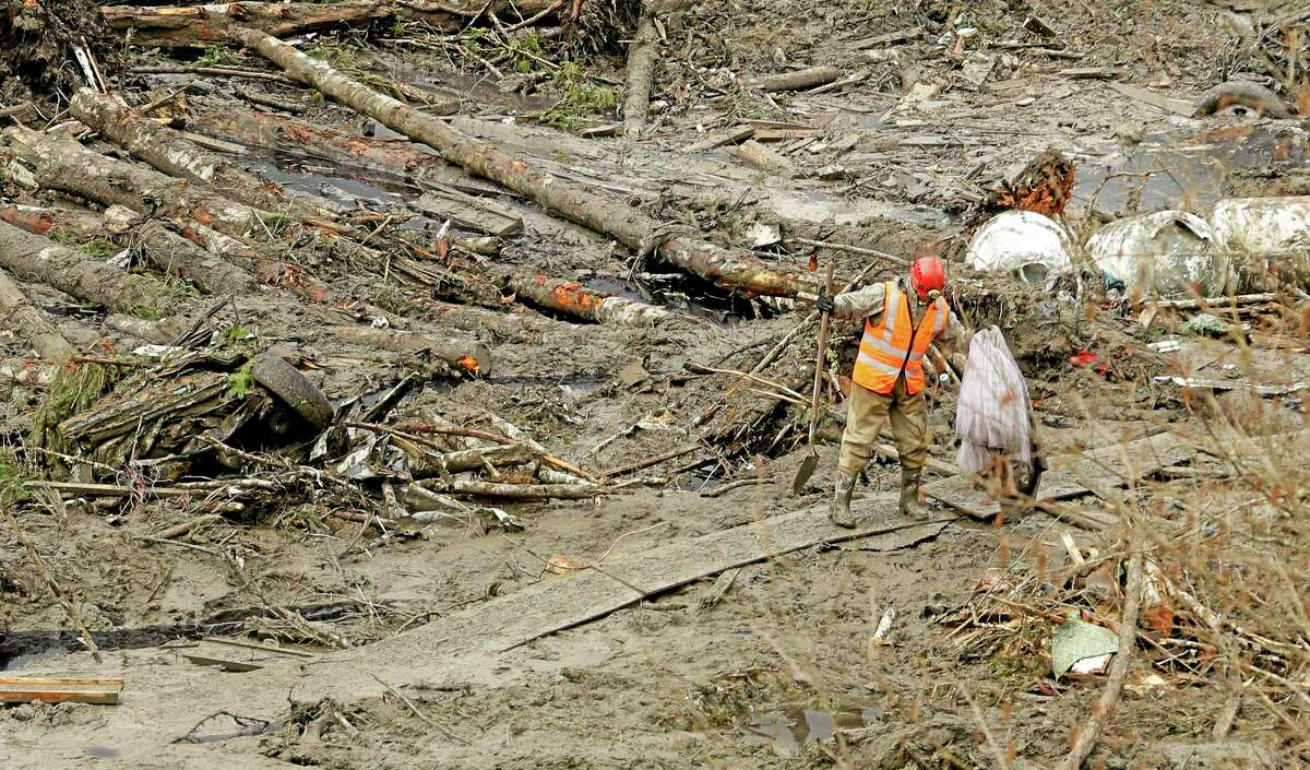 A worker carries a recovered item along a plywood walkway through other debris, Sunday, March 30, 2014, as search work continues at the site of the massive mudslide that struck the community of Oso,Wash. on March 22, 2014. (AP Photo/Ted S. Warren)