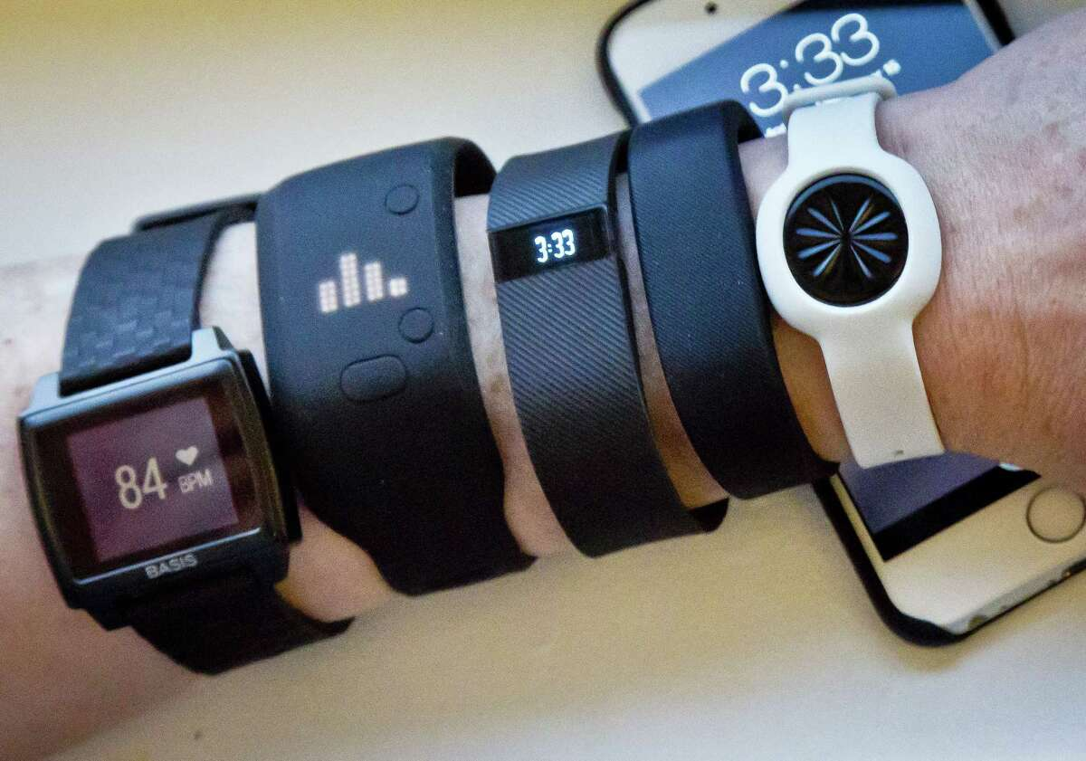 Fitness trackers, from left, Basis Peak, Adidas Fit Smart, Fitbit Charge, Sony SmartBand and Jawbone Move are posed for a photo next to an iPhone, in New York.
