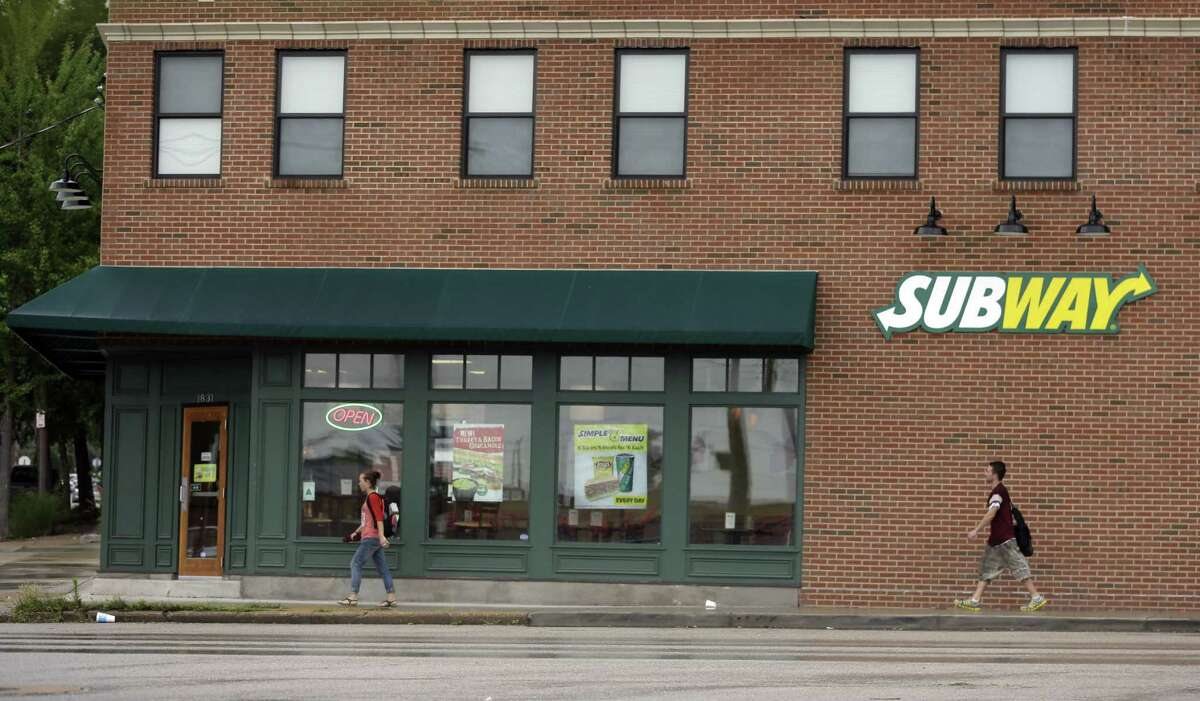 People walk past a Subway restaurant in St. Louis.