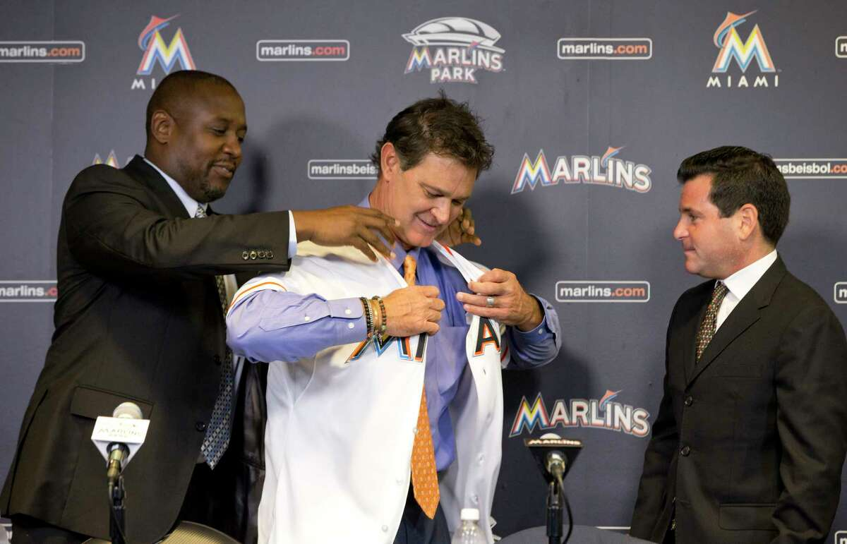 Michael Hill, left, president of baseball operations for the Miami Marlins, helps Don Mattingly put on a jersey as team president David Samson, right, looks on after Mattingly was introduced as manager on Monday in Miami.