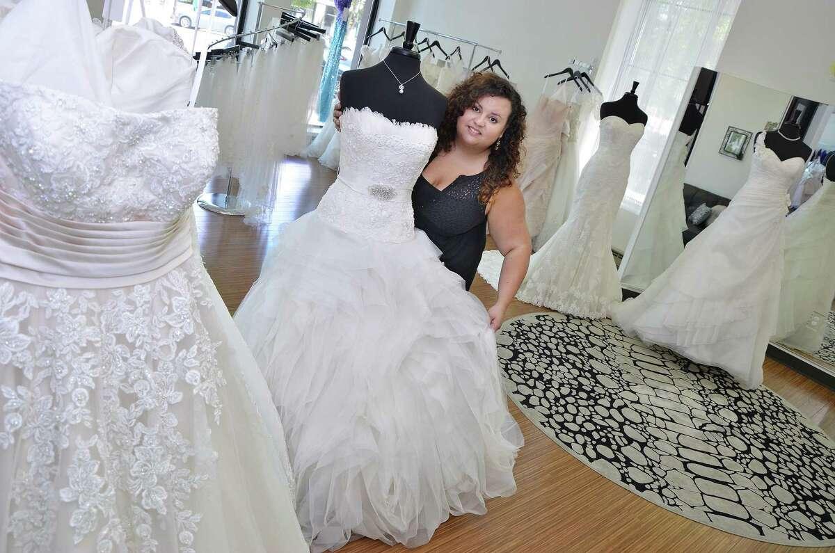 Krista Lastrina Matthews, owner of Lastrina Girls Bridal Salon displays the La Sposa bridal gown from Spain Friday afternoon.