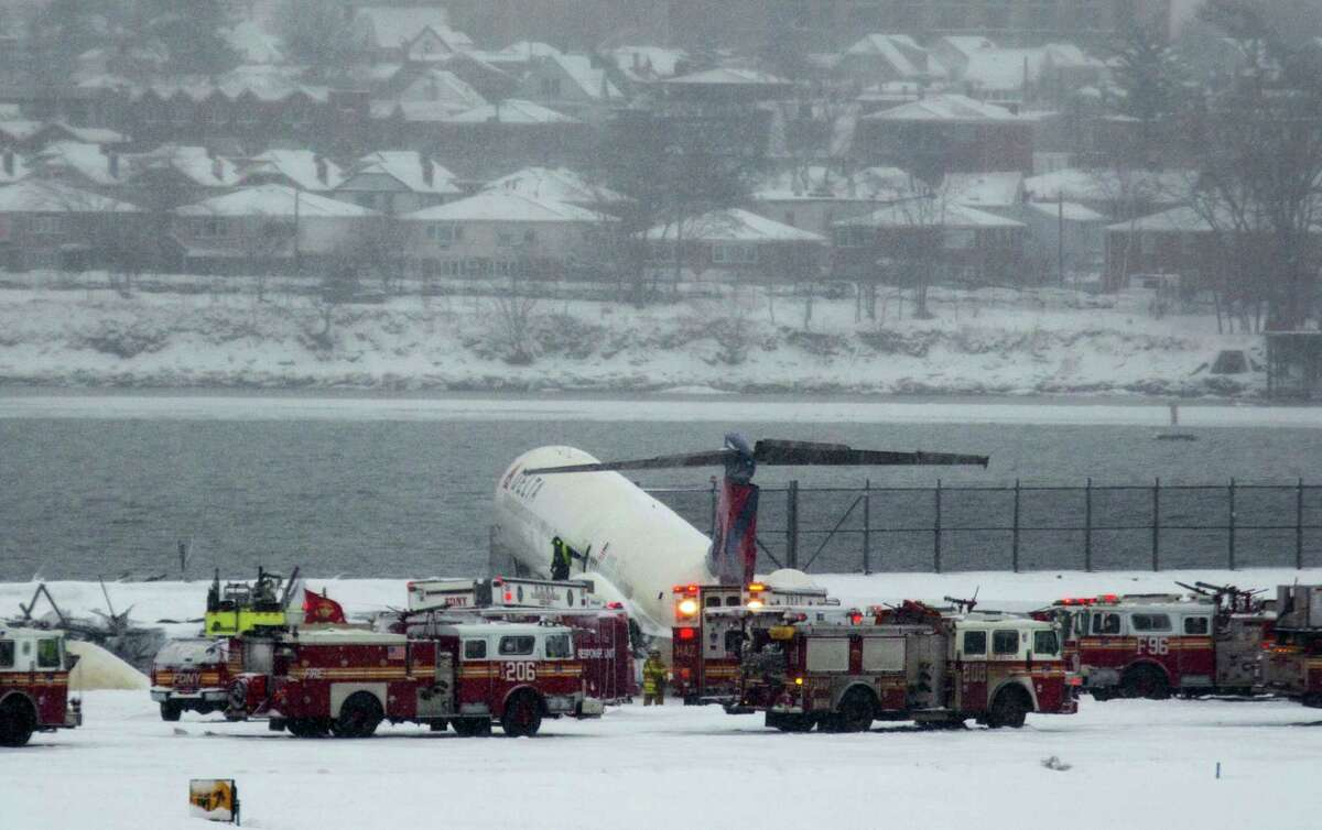 A Delta plane rests on a berm near the water at LaGuardia Airport in New York, Thursday, March, 2015. Delta Flight 1086, carrying 125 passengers and five crew members, veered off the runway at around 11:10 a.m., authorities said. Six people suffered non-life-threatening injuries, said Joe Pentangelo, a spokesman for the Port Authority of New York and New Jersey, which runs the airport.