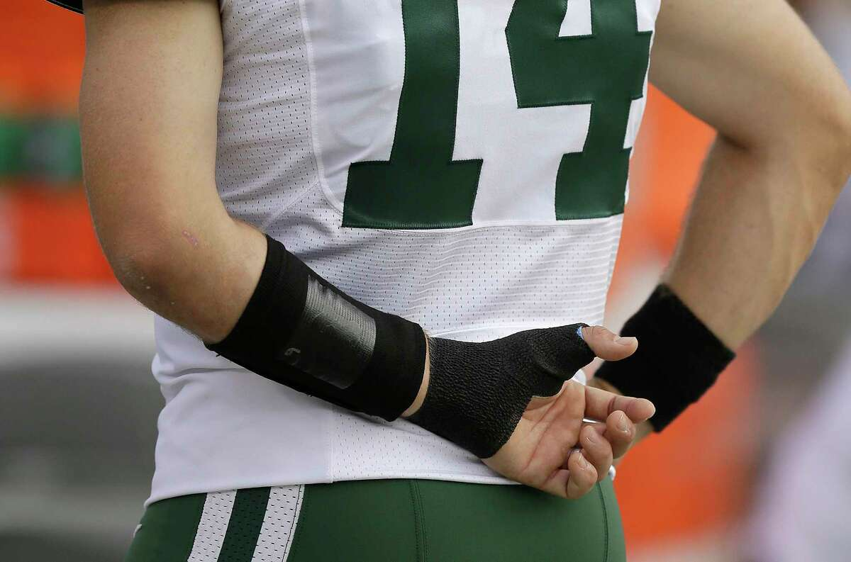 New York Jets quarterback Ryan Fitzpatrick, who left the game after injuring his left hand, stands on the sideline during Sunday's game against the Raiders in Oakland, Calif.