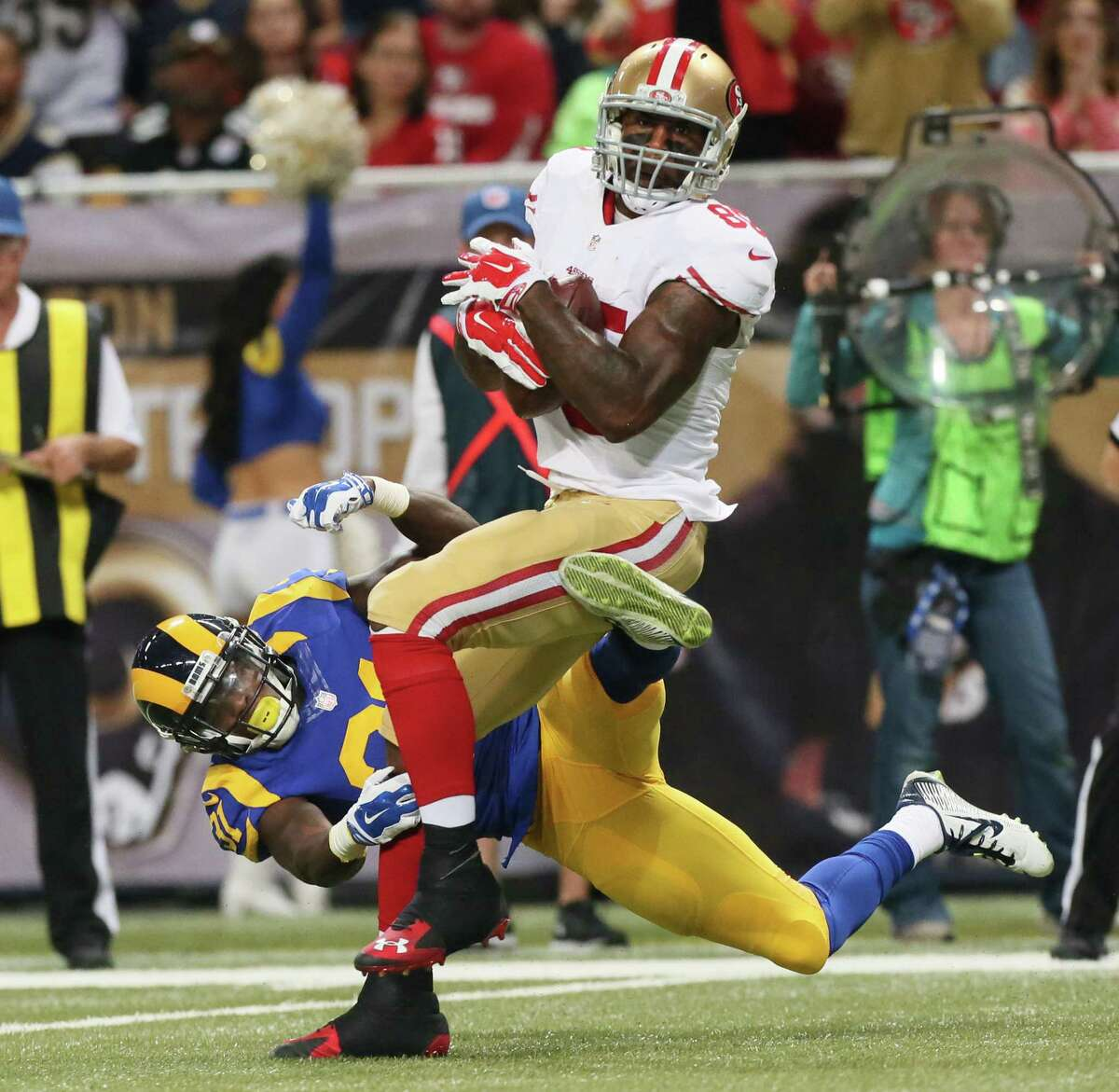 San Francisco 49ers tight end Vernon Davis tries to break free of a tackle by Rams safety Maurice Alexander during Sunday's game in St. Louis.