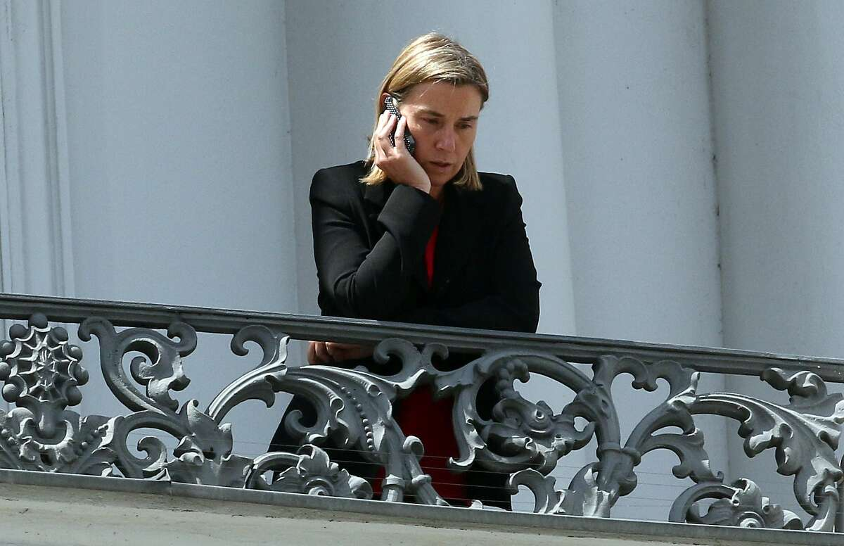 European Union High Representative Federica Mogherini make a phone call on a balcony of the Palais Coburg where closed-door nuclear talks with Iran take place in Vienna, Austria, Friday, July 10, 2015. (AP Photo/Ronald Zak)