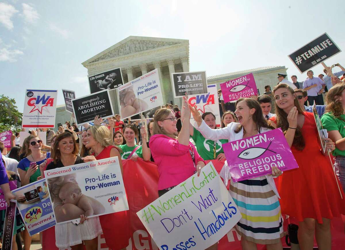 Demonstrators react to hearing the Supreme Court's decision on the Hobby Lobby case outside the Supreme Court in Washington, D.C., June 30. The Supreme Court says corporations can hold religious objections that allow them to opt out of the new health law requirement that they cover contraceptives for women.