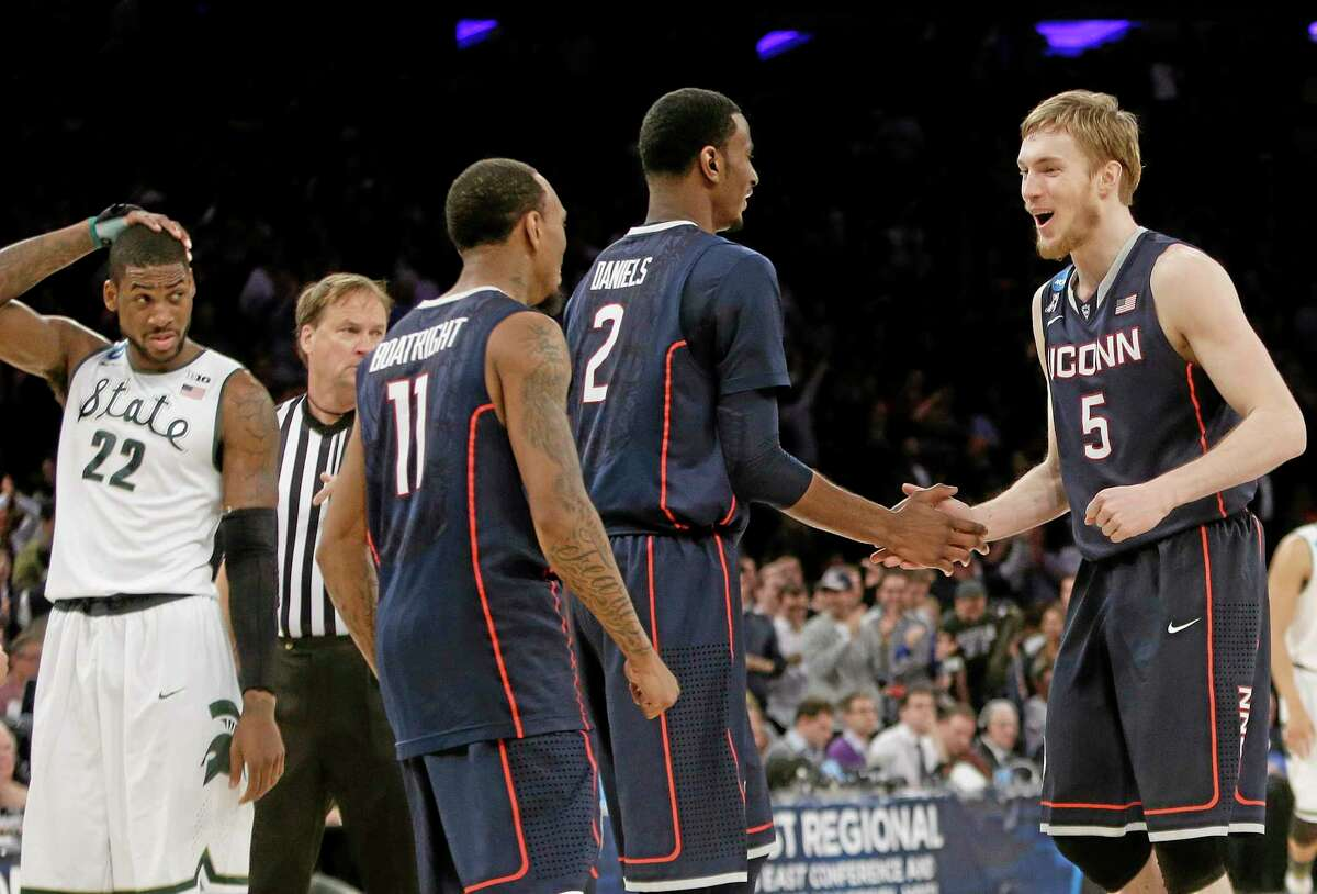 Connecticut's Niels Giffey (5), of Germany, celebrates with teammates DeAndre Daniels (2) and Ryan Boatright (11) as Michigan State's Branden Dawson (22) watches during the second half of a regional final in the NCAA college basketball tournament on Sunday, March 30, 2014, in New York. Connecticut won the game 60-54. (AP Photo/Frank Franklin II)