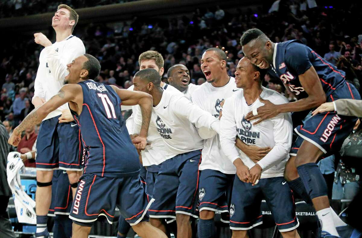 Connecticut's Ryan Boatright (11) and Amida Brimah (35) celebrate with teammates during the second half of a regional final against Michigan State in the NCAA college basketball tournament, Sunday, March 30, 2014, in New York. Connecticut won 60-54. (AP Photo/Frank Franklin II)
