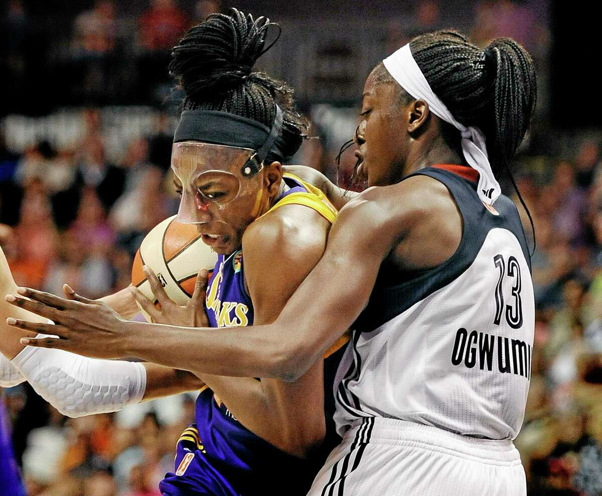 The Los Angeles Sparks' Nneka Ogwumike, left, is guarded by her sister Chiney, right, of the Connecticut Sun during the first half Sunday in Uncasville.