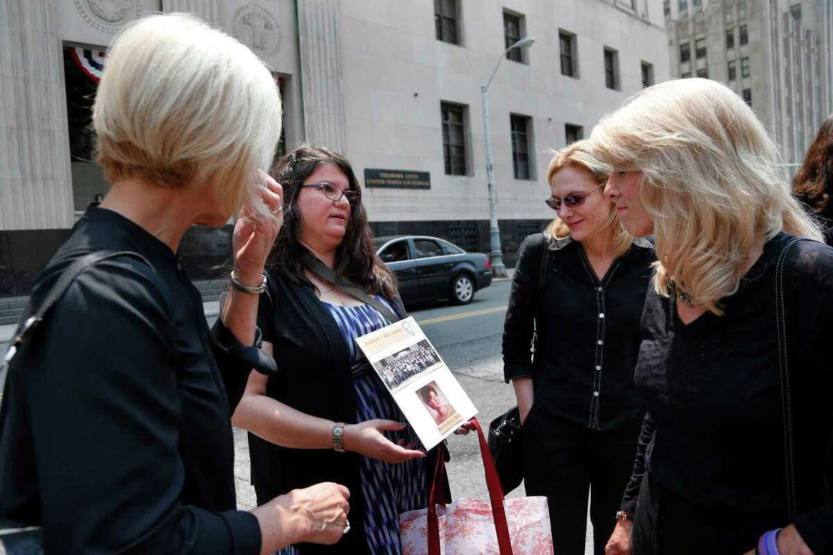 """Liz Lupo, second from left, shows a sign in honor of her mother, Marianne Lupo, a former patient of Dr. Farid Fata, outside federal court, Monday, July 6, 2015, in Detroit. Patients of Fata received """"stunning"""" doses of a powerful, expensive drug that exposed them to life-threatening infections, an expert testified Monday as a judge heard details about a cancer specialist who fleeced insurance companies and harmed hundreds of people. (AP Photo/Paul Sancya)"""
