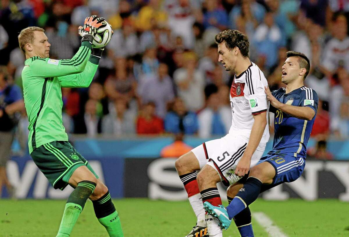 Germany's goalkeeper Manuel Neuer, left, makes a save as Germany's Mats Hummels and Argentina's Sergio Aguero, right, look on during the World Cup final Sunday.
