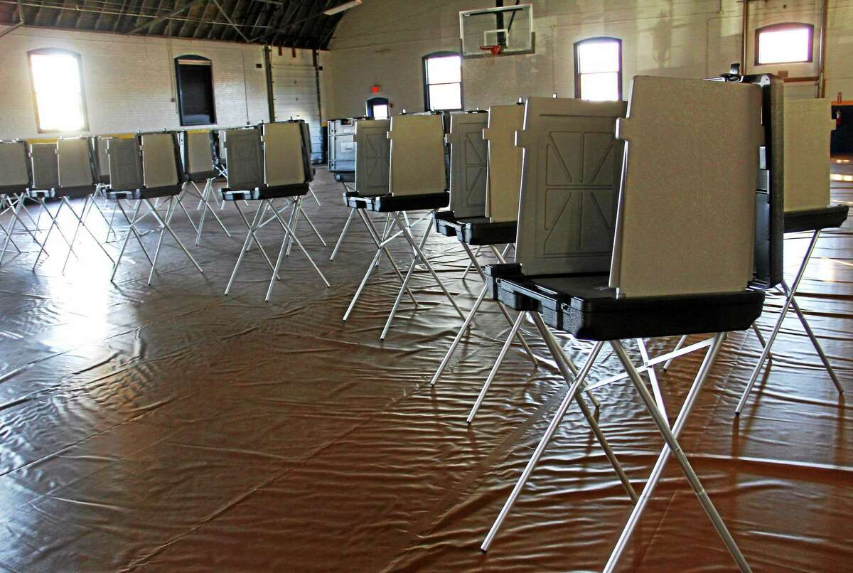 Several voting booths stand inside an empty gym at the Torrington Armory on Monday, Nov. 4, 2013., in Torrington. The armory is one five polling places for Torrington voters. Esteban L. Hernandez Register Citizen