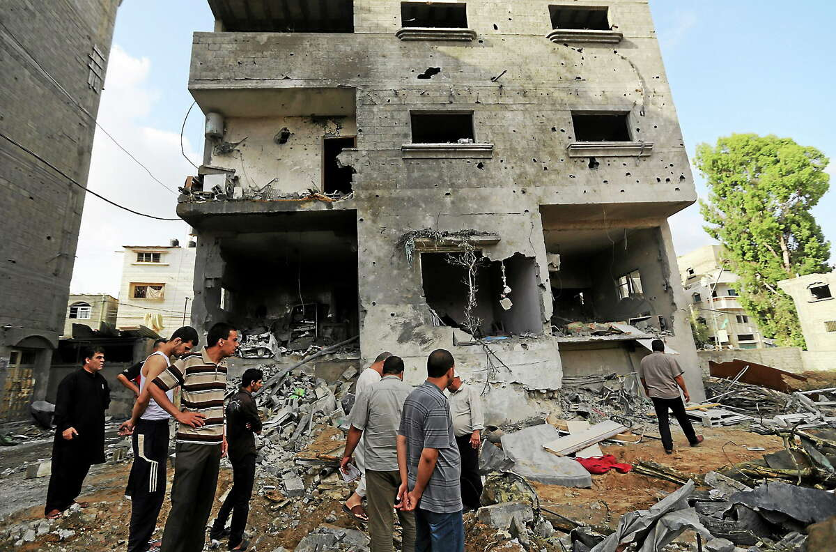 Palestinians gather outside the damaged house of Gaza's police chief Taysir al-Batsh after it was hit by an Israeli missile strike in Gaza City on July 13, 2014.