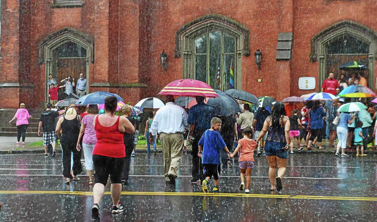 Catherine Avalone — New Haven Register Rain forced the community to walk to the South Congregational Church to hold a vigil for Aaden Moreno July 8.