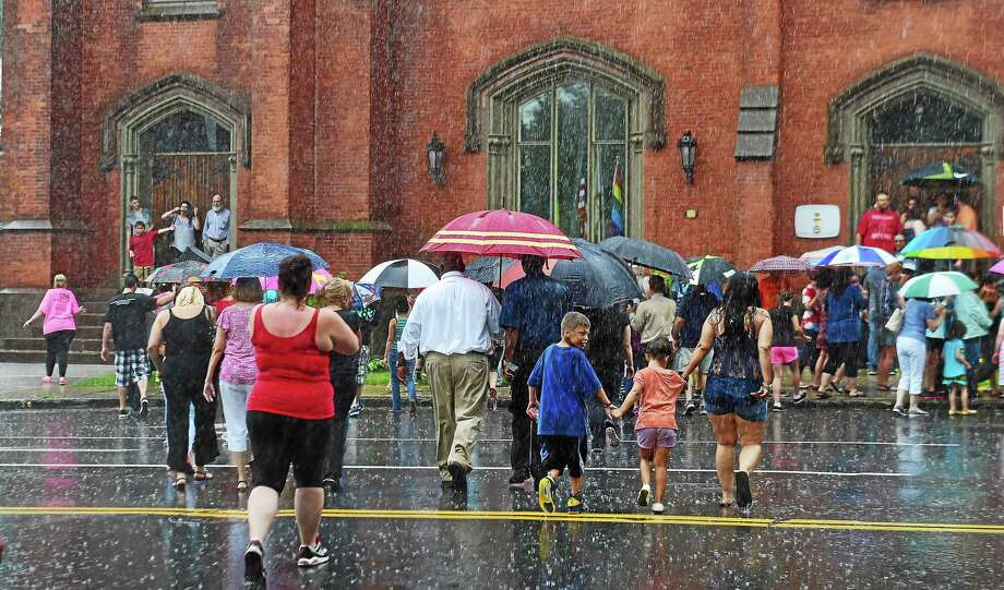 Catherine Avalone — New Haven Register  Rain forced the community to walk to the South Congregational Church to hold a vigil for Aaden Moreno July 8. Photo: Journal Register Co. / New Haven RegisterThe Middletown Press