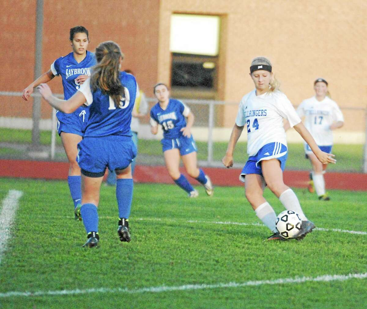 East Hampton junior Kayla McLaughlin takes a shot as Old Saybrook defenders Erin Stangel and Maggie Smith (19) move in.
