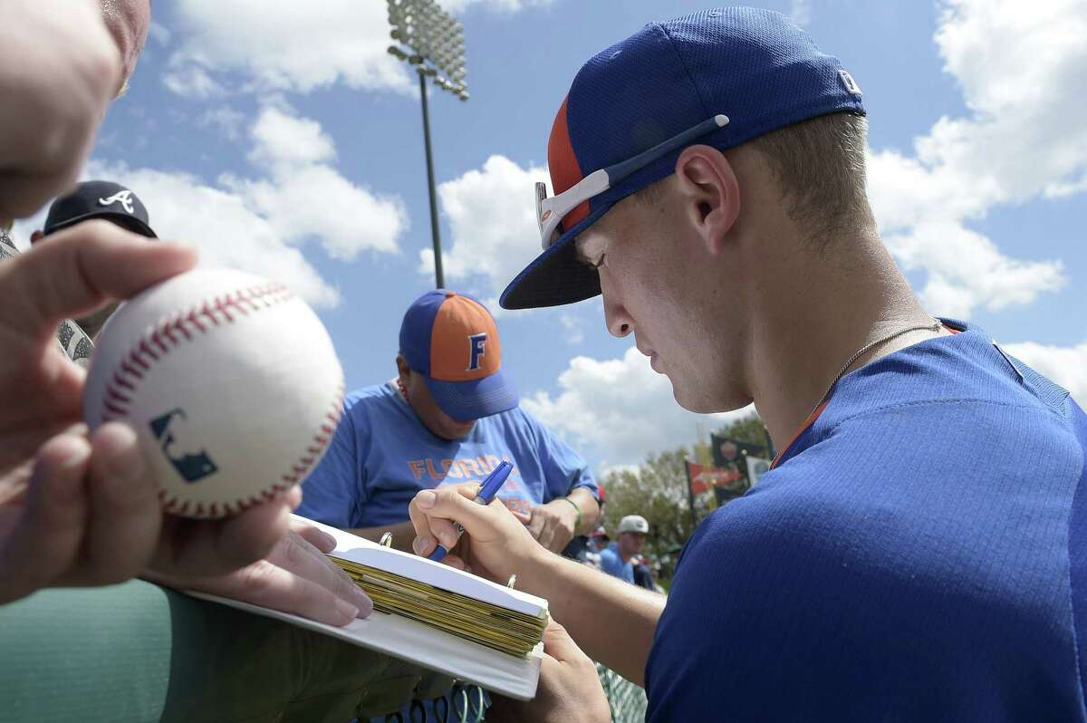 The New York Mets' Brandon Nimmo signs autographs for fans before a spring training game against the Atlanta Braves on Wednesday in Kissimmee, Fla.