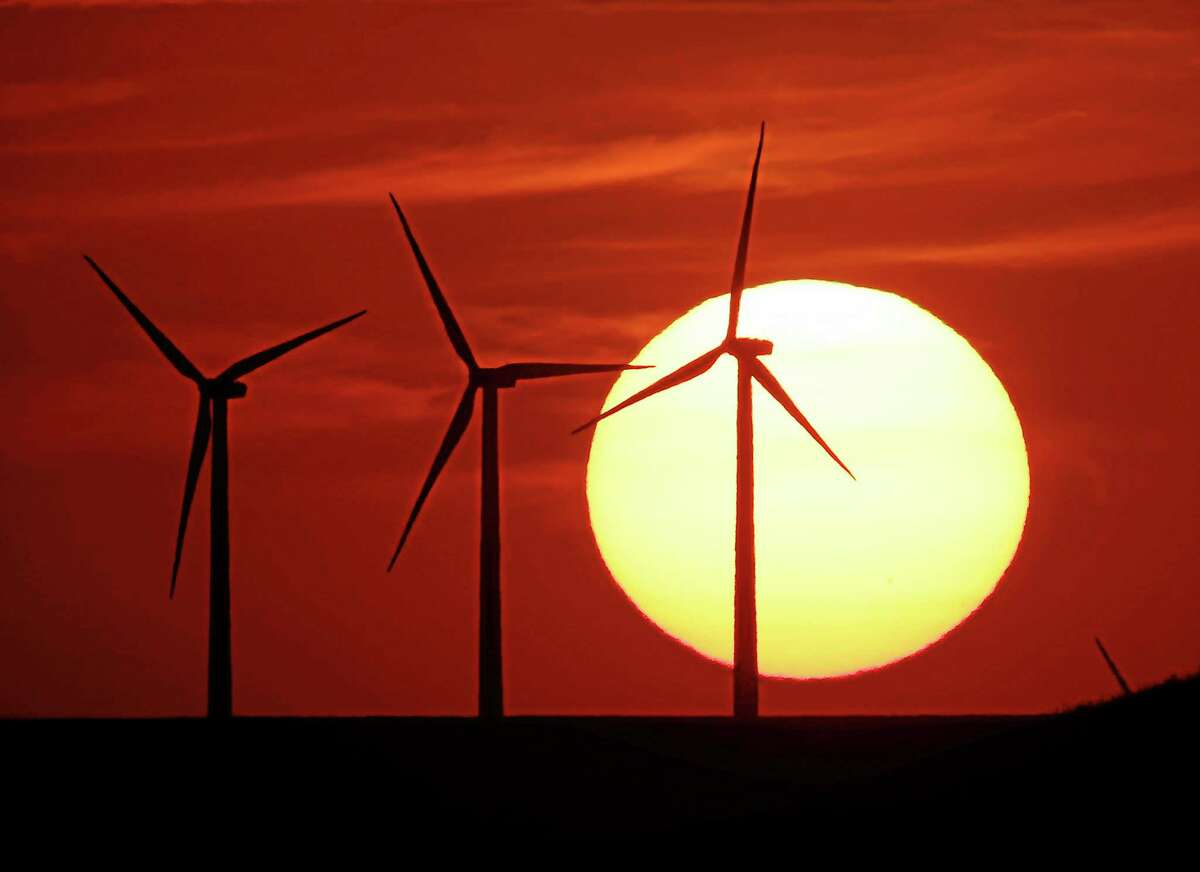 In this Aug. 23, 2013 file photo wind turbines are silhouetted by the setting sun as they produce electricity near Beaumont, Kan.