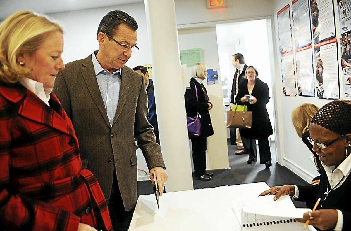 Gov. Dannel P. Malloy, center and wife Cathy, left, check in to vote Tuesday in Hartford. Malloy is facing Republican candidate Tom Foley in today's election.