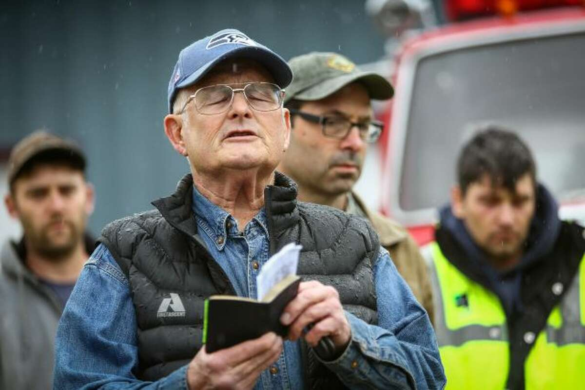 Rev. Michael De Luca offers a prayer before rescue workers and volunteers pause during a state-wide moment of silence to honor the victims of the Oso mud slide in front of the Darrington, Wash., on Saturday, March 29, 2014. Gov. Jay Inslee had asked people across Washington to pause at 10:37 a.m. The huge slide that destroyed a neighborhood in Oso north of Seattle struck at that time on March 22. Authorities say they've found at least 25 bodies and scores remain missing. (AP...
