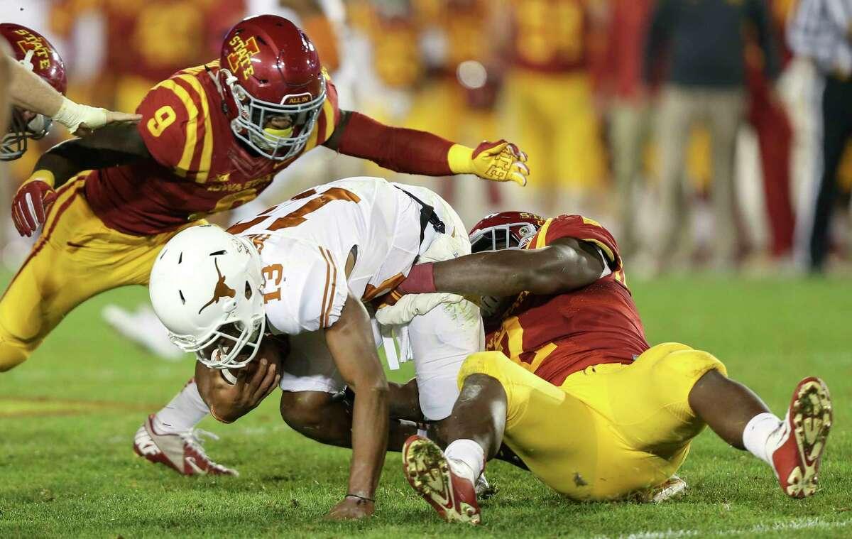 Texas quarterback Jerrod Heard is brought down by Iowa State linebackers Jordan Harris and Reggan Northrup on Saturday.